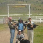 Here's a spectacular view of Mount Shasta through the ranch gates. Standing from left to right are Daniel W. Pinkham with Smoochie, Alexey Steele and Peter Adams with Panda. Kneeling in front is Frank Serrano with Jaipur and Lefty Loo.